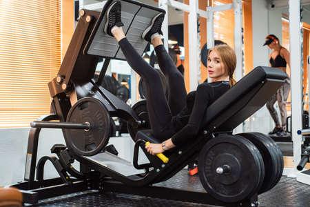 Young sporty woman does leg exercises on leg press machine