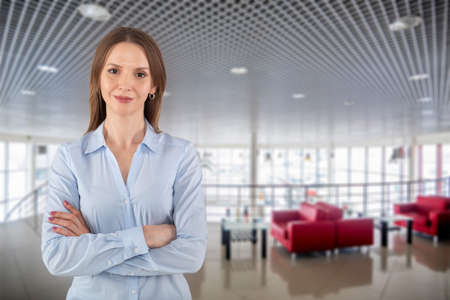 Beautiful young business woman with crossed arms on empty dealer center background