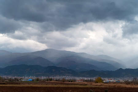 Gray sky with storm clouds over the mountains