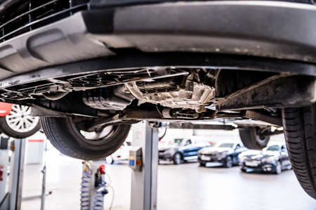 Close up of chassis or wheels or motor on lift on Service station. Фото со стока