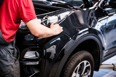 Male car mechanic at autosalon hands on black car business class at autoservice Фото со стока
