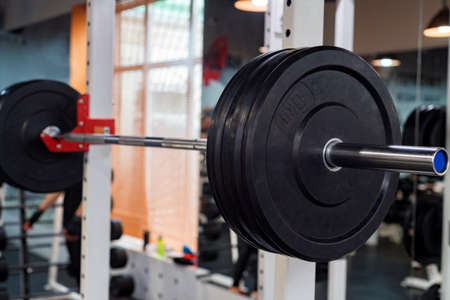 Fitness dumbbell and barbell weight plates in modern gym Фото со стока