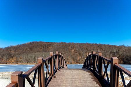 Narrow metal and wood foot bridge across river in autumn