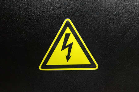 Sign of high voltage on a black metal Фото со стока