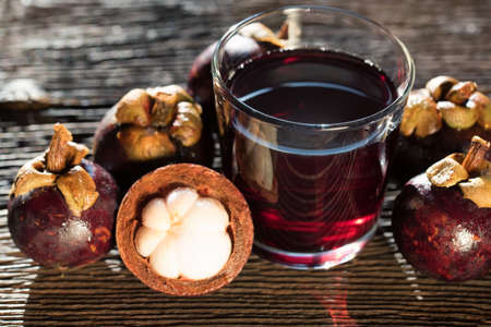 Fresh Mangosteen fruit and drink in jar on wooden background