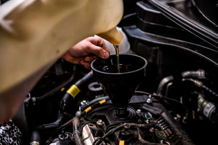 Close-up of mechanic adding oil with a funnel Stockfoto