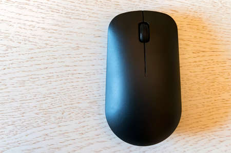 Close up of wireless computer mouse on white wooden background