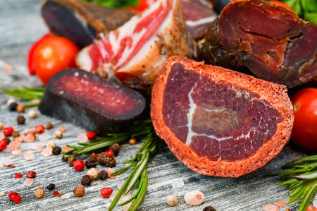 Close up of assorted dry-cured meat on the wooden background