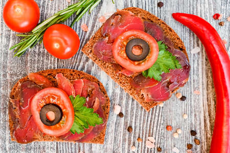 Close up of sliced dry-cured meat on the wooden background