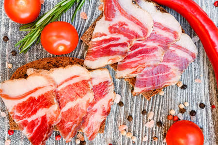 Close up of sliced bacon sandwitches on the wooden background Foto de archivo