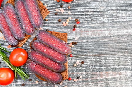 Close up of sliced cured sausage on the wooden background