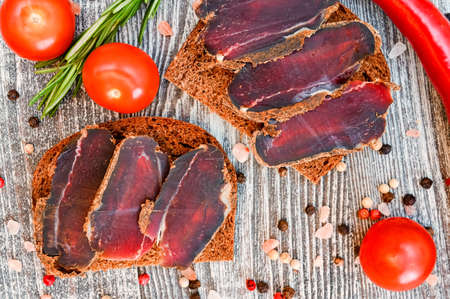 Close up of sliced dry-cured venison on the wooden background