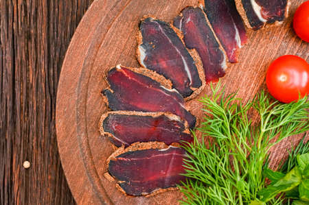 Close up of assorted sliced dry-cured meat on the wooden plate background