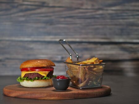 vegan plant based burger with fries served on wooden tray
