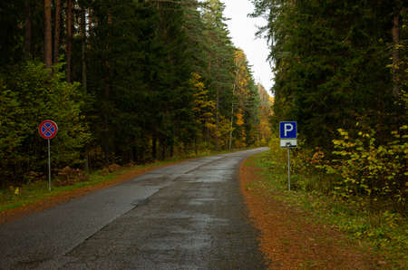 Autumn in the forest asphalt road with a parking and forbidden  to stand signs, car
