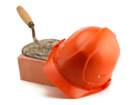 housebuilding: Orange helmet red brick and trowel Stock Photo