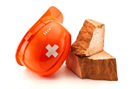 housebuilding: Orange helmet  with cross shaped court plaster and broken brick isolated on white
