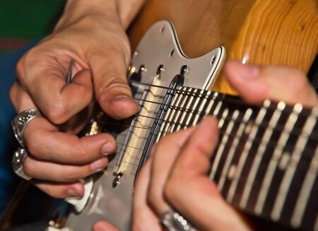 instrumentalist: Guitarist hands playing on electro guitar. Close-up.