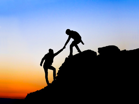challenging: Silhouette of helping hand between two climber Stock Photo