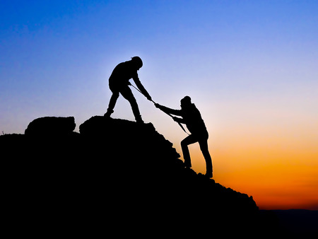 between: Silhouette of helping hand between two climber Stock Photo