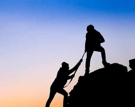 alps: Silhouette of helping hand between two climber Stock Photo