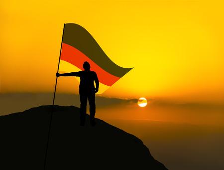 Silhouette Mann Gewinner winken Deutschland Flagge oben auf dem Berggipfel Standard-Bild - 89766700
