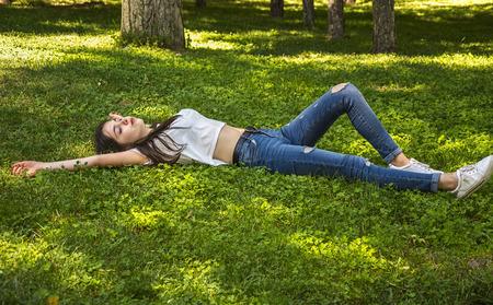 Relaxing girl lying on the grass. Zdjęcie Seryjne - 97763671