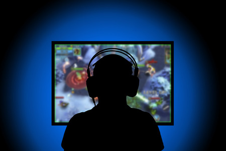 Silhouette,Young man playing video games on pc at home
