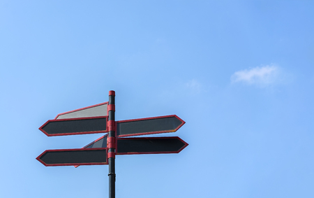 Blank directional road signs against blue sky. Black red arrows on the signpost