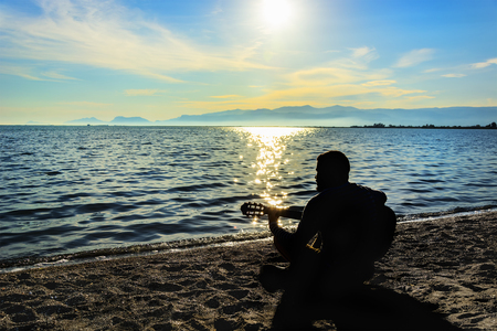 Silhouette.Young men playing guitar while sitting on the beach. Reklamní fotografie