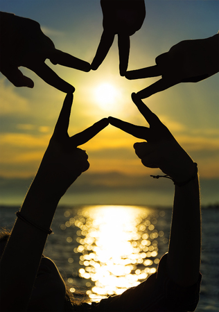 Many hands connecting to star shape at sunset, Teamwork Concept Reklamní fotografie
