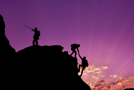 Hikers climbing on rock, mountain at sunset, one of them giving hand and helping to climb.Teamwork , Helps ,Success, winner and Leadership concept .