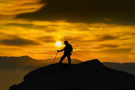 Silhouette of a rock climber on the peak. Sport and active life concept