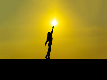 silhouette-young girl touching the sun at sunset Reklamní fotografie
