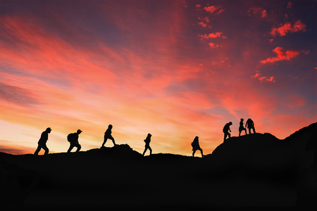 eight friends walk on mountain path in sunset