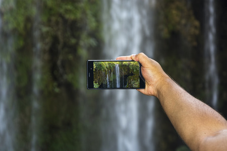 Taking picture of waterfall lansdcape with smart phone.