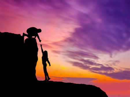 Silhouettes de deux personnes grimpant sur la montagne et aidant. Banque d'images