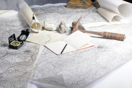 The geological expedition is prepared with the study of topographic maps  On the table the tools of the geologist