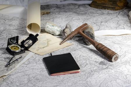 地質探険は地質学者のツールのテーブルの上の地形図の研究と準備します。