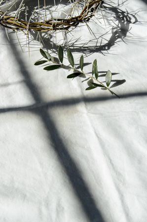 crown of thorns reminds the passion of the christ. resting on a white linen cloth with an olive branch