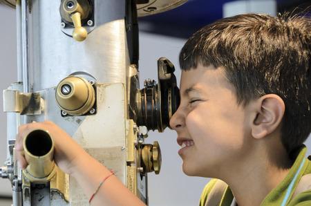 Bambino curioso guardando attraverso il periscopio l'ambiente esterno.