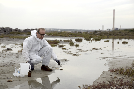 soil pollution: Worker in a protective suit examining pollution in the water at the industry.