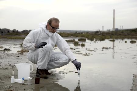 bureta: Trabajador en un traje de protección examinar la contaminación en el agua en la industria. Foto de archivo