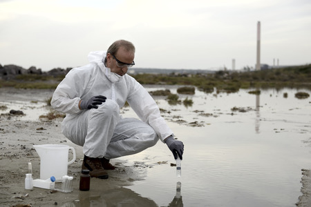burette: Worker in a protective suit examining pollution in the water at the industry.