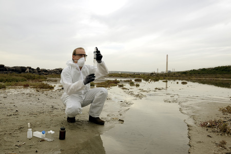 contaminacion del agua: Trabajador en un traje de protecci�n examinar la contaminaci�n en el agua en la industria. Foto de archivo