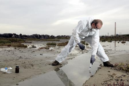 Operaio in una tuta protettiva esaminando l'inquinamento in acqua al settore. Archivio Fotografico - 35277604