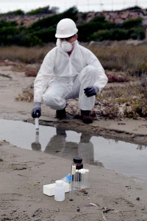 업계에서 물 오염을 검사하는 보호 복에서 노동자.
