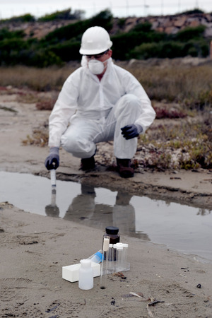 Worker in a protective suit examining pollution in the water at the industry.