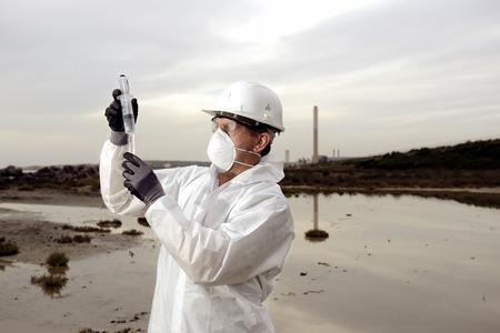業界での水の汚染を調べる防護服の労働者。