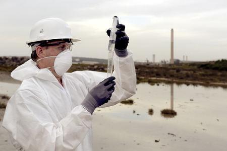 reclamation: Worker in a protective suit examining pollution in the water at the industry.